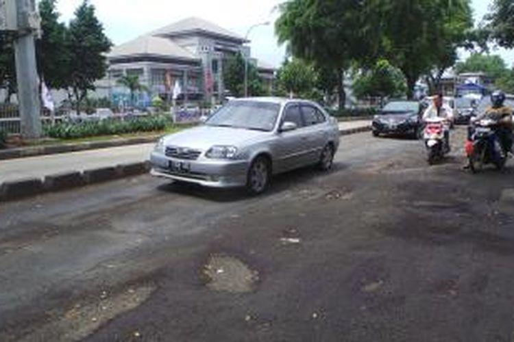 Jalan Bekasi Raya Timur seberang kantor Imigrasi Jakarta Timur arah Klender, rusak dan mengganggu laju lalu lintas kendaraan. Jumat (6/2/2015).