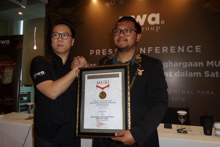 CEO dan Founder Kopi Janji Jiwa Billy Kurniawan (kiri) saat menerima penghargaan dari Museum Rekor Dunia Indonesia (MURI). Kopi Janji Jiwa mendapatkan penghargaan untuk rekor Pertumbuhan Kedai Kopi Tercepat dalam Satu Tahun.