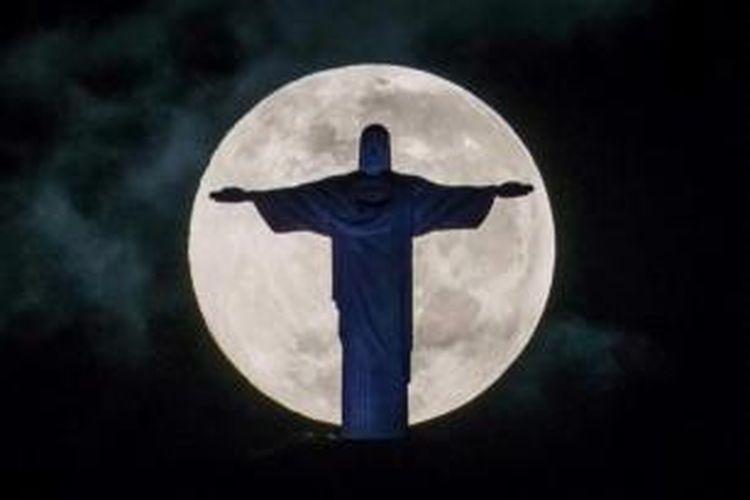 Bulan purnama dengan latar depan patung Kristus Penebus di atas bukit Corcovado di Rio de Janeiro, Brasil, 25 Mei 2013. Paus Francis akan mengunjungi Rio de Janeiro selama acara World Youth Day pada 23-28 Juli.