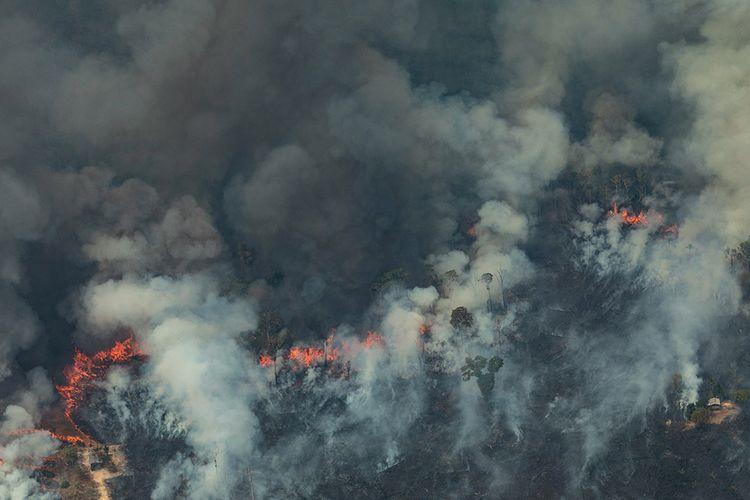 Foto udara menunjukkan asap mengepul dari kebakaran hutan di Kota Candeias do Jamari, Amazon, Brasil, Sabtu (24/8/2019). Kebakaran hutan Amazon menjadi sorotan dunia setelah api yang menjalar di paru-paru dunia itu mencapai 18.627 kilometer persegi tahun ini, dengan 76.720 kebakaran terjadi dari Januari-Agustus.