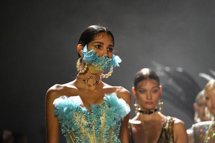Seorang model dari pagelaran the Blonds mengenakan masker.