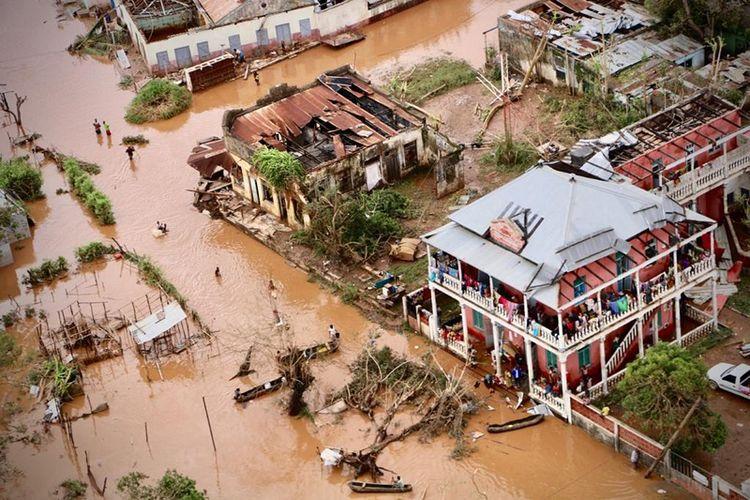 Warga terpaksa berjalan di jalanan kota Buzi, wilayah tengah Mozambik yang masih digenangi banjir usai dihantam badai tropis Idai.