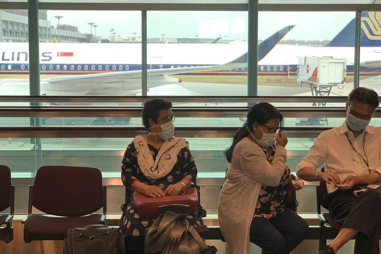 Penumpang mengenakan masker untuk melindungi diri dari penyebaran Covid-19 coronavirus, saat menunggu penerbangan di Bandara Internasional Changi, di Singapura, 10 Februari 2020.