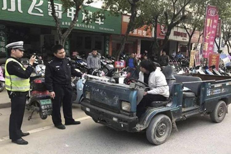Polisi menahan Huang saat mengemudikan bagian bawah tank miliknya.