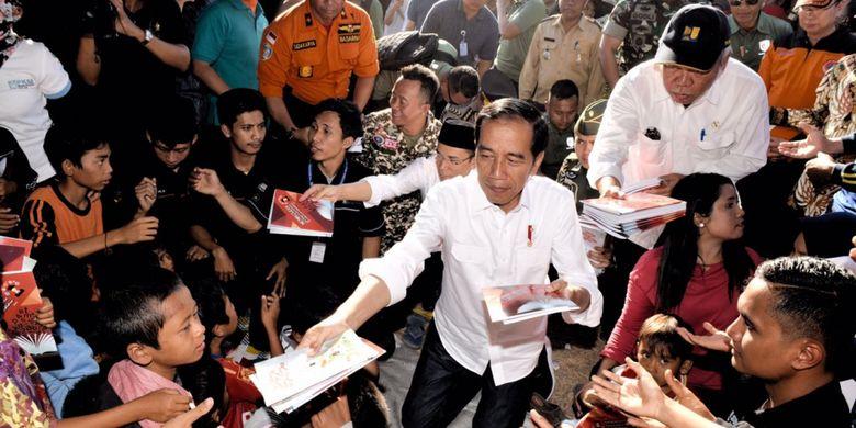 Presiden Joko Widodo membagikan buku tulis bagi anak-anak korban gempa di Desa Madayin, Kecamatan Sambelia, Kabupaten Lombok Timur, NTB, Senin (30/7/2018).