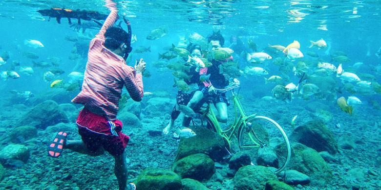 Pengunjung Umbul Ponggok di Kecamatan Polanharjo, Kabupaten Klaten, Jawa Tengah, menyewa jasa warga setempat yang berprofesi sebagai fotografer bawah air, Minggu (14/8/2016).