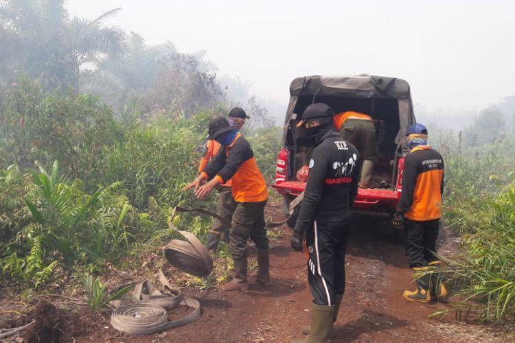 Petugas gabungan Manggala Agni Dumai berupaya melakukan pendinginan kebakaran lahan yang terjadi di Dumai