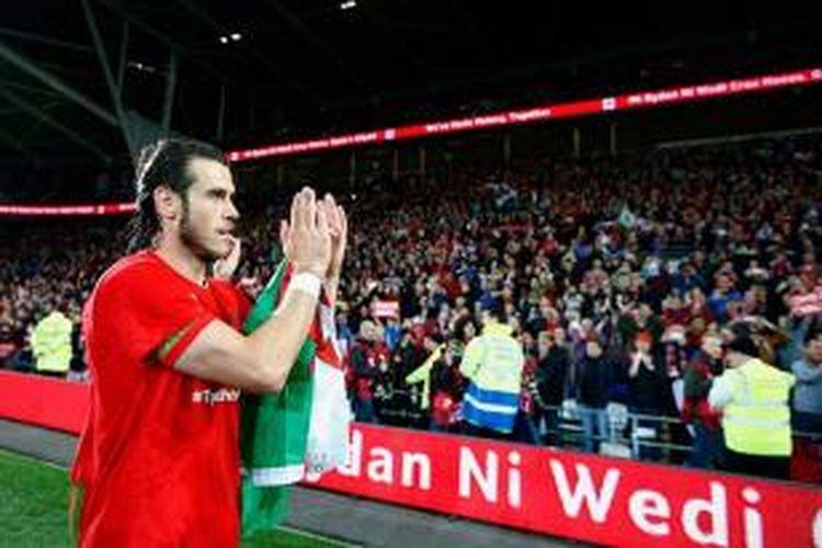Gareth Bale memberi aplaus kepada penonton yang menjadi sumber kekuatan Wales lolos ke Piala Eropa 2016, Selasa (13/10/2015).