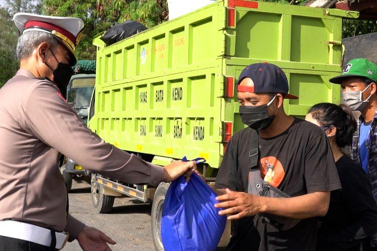 Salah satu personel Polda Bali saat memberikan sembako kepada pengguna jalan yang melintas.