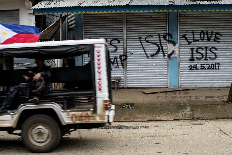 Sebuah mobil patroli tentara Filipina melintasi sebuah bangunan yang sudah dihiasi grafiti pro-ISIS.
