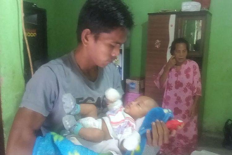Febrianto menggendong bayi Delfa saat ditemui di rumahnya, Selasa (14/1/2020). Bayi Delfa sudah berada di rumah usai diperbolehkan pulang setelah 3 bulan ditahan pihak RS. Bayi Delfa dikebalikan ke orangtuanya setelah ada pihak donatur melunasi tagihan rumah sakit Febrianto dan Yularmi, istrinya.