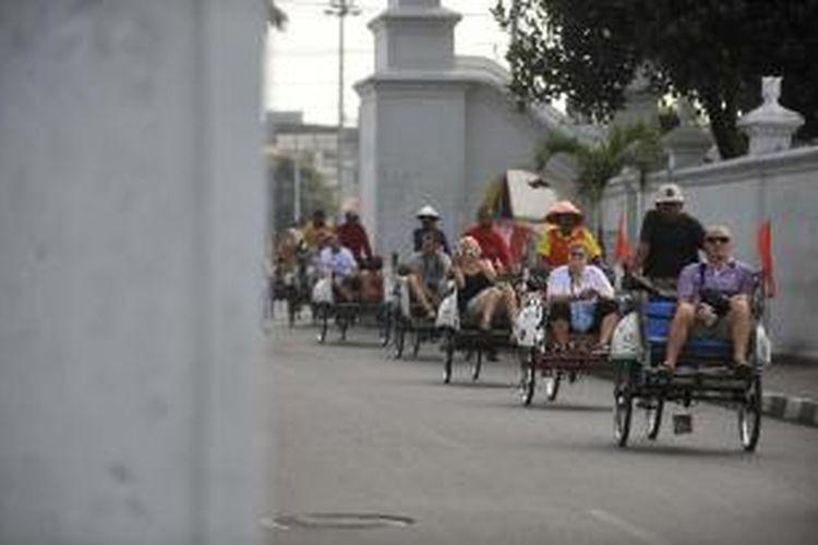 Wisatawan asing melewati Jalan Rotowijayan saat menikmati pemandangan Kota Yogyakarta dari atas becak, Rabu (1/8/2012).