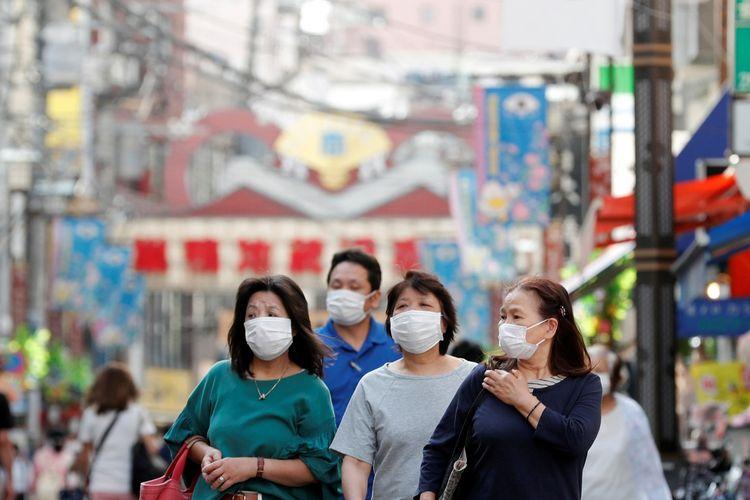Warga memakai masker pelindung berjalan di sebuah distrik pasar lokal di tengah penyebaran penyakit virus korona (COVID-19) di Tokyo, Jepang, Rabu (13/5/2020).