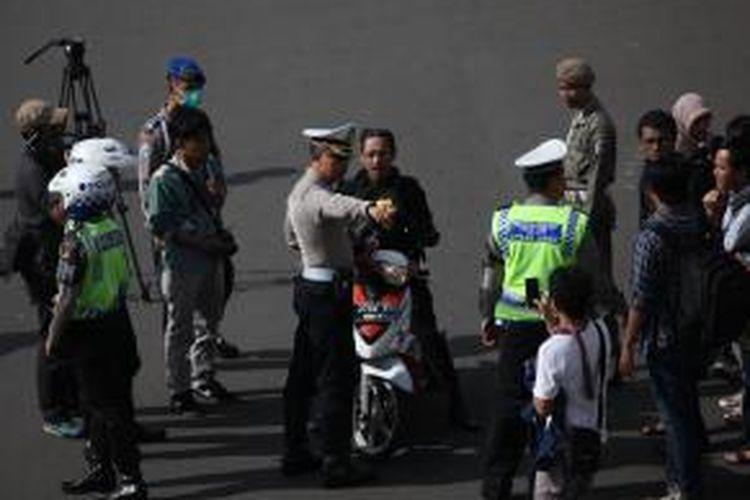 Gabungan petugas kepolisian dan Dinas Perhubungan DKI mengarahkan pengendara sepeda motor yang akan melintas di Jalan MH Thamrin, Jakarta Pusat, Rabu (17/12/2014). Di hari pertama uji coba pembatasan sepeda motor sepanjang Jalan Thamrin-Medan Merdeka Barat, masih terdapat sejumlah pengendara yang belum mengetahui aturan tersebut. KOMPAS/LUCKY PRANSISKA