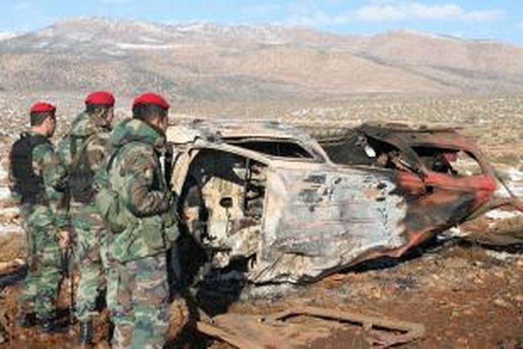 Tentara Lebanon memeriksa bangkai mobil yang meledak di desa Sbouba, Lembah Bekaa tak jauh dari pos pemeriksaan Hezbollah, Selasa (17/12/2013).