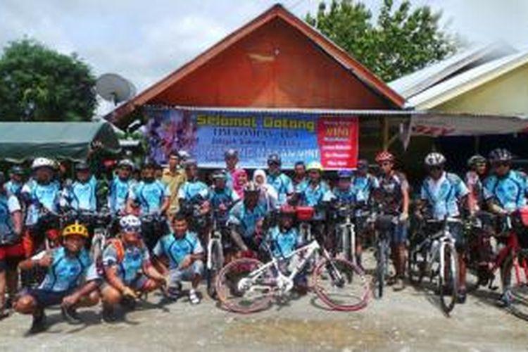 Peserta Jelajah Sepeda Sabang-Padang Kompas-PGN foto bersama dengan pemilik warung makan di Nagan Raya, Aceh, Selasa (3/9/2013).