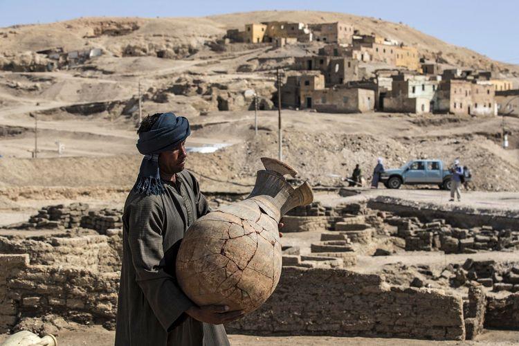 Sebuah foto bertanggal 10 April 2021 menunjukkan seorang pekerja membawa pot yang ditemukan di Kota Emas Firaun Mesir.  Julukan The Rise of Aden didirikan pada masa pemerintahan Amanhotep III dan menghilang 3.000 tahun yang lalu.