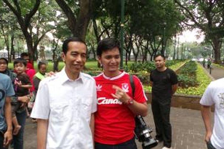 Gubernur DKI Jakarta Joko Widodo tampak sedang melayani ajakan berfoto bersama warga di Taman Suropati, Menteng, Jakarta Pusat, Minggu (21/7/2013).