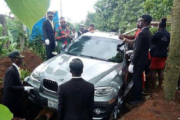 Azubuike (tengah, berbaju merah-hijau) memperhatikan prosesi pemakaman ayahnya menggunakan mobil BMW X5 seharga Rp 1,2 miliar.