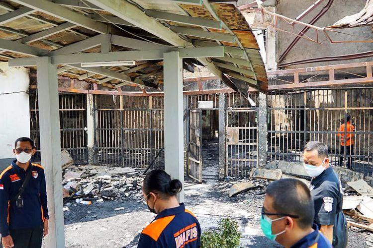 Dalam foto yang dirilis oleh Kementerian Hukum dan Hak Asasi Manusia Republik Indonesia ini, petugas polisi memeriksa sel-sel yang rusak setelah kebakaran di Penjara Tangerang di Tangerang, Indonesia, Rabu, 8 September 2021.