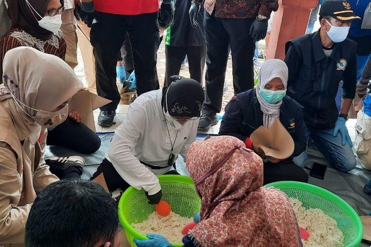 Menteri Sosial Tri Rismaharini membantu proses pembungkusan nasi bungkus untuk korban banjir di Jember, Senin (18/1/2021)