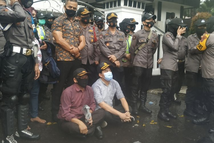 Dua anggota DPRD duduk bersama demonstran di bawah guyuran hujan di depan gedung DPRD Kota Sukabumi, Jawa Barat, Kamis (15/10/2020).