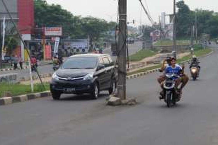 Sebanyak empat tiang listrik berdiri di tengah Jalan Raya Ciater, Tangerang Selatan, Selasa (31/5/2016). Keberadaan tiang listrik di tengah jalan ini kerap membuat pengendara terlibat kecelakaan di daerah tersebut.
