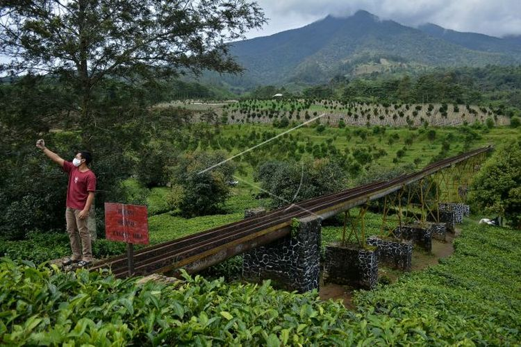Pengunjung berswafoto di jembatan irigasi air peninggalan zaman kolonial Belanda, kawasan Perkebunan PTPN VIII Dayeuhmanggung, Cilawu, Kabupaten Garut, Jawa Barat, Jumat (22/01/2021). Jembatan irigasi air sepanjang 200 meter yang dibangun pada tahun 1913 oleh kolonial Belanda tersebut menjadi daya tarik wisatawan dengan suasana perkebunan teh dan pemandangan gunung Cikuray (ANTARA FOTO/Candra Yanuarsyah/agr/rwa).