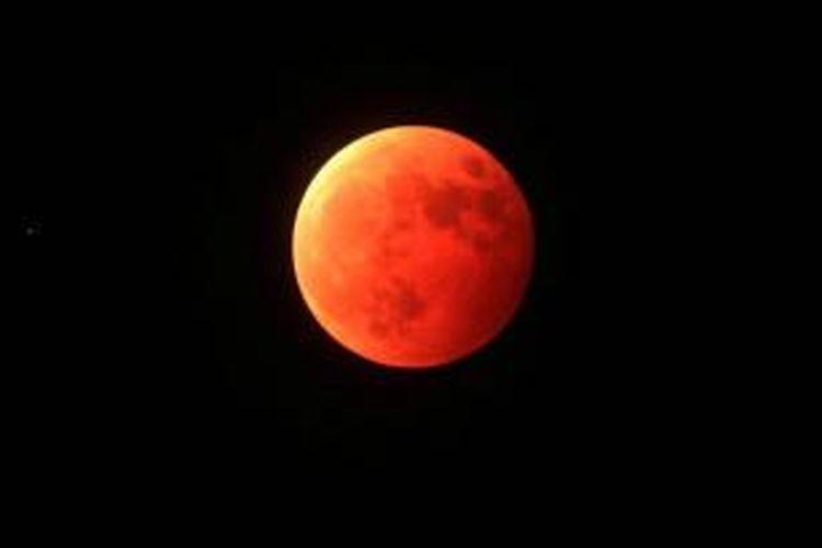 Gerhana bulan terlihat di langit kota Qingdao, provinsi Shandong, China, 8 Oktober 2014. Warna merah pada gerhana bulan dipengaruhi oleh pembiasan atmosfer Bumi, disebut dengan 'bulan merah darah'.