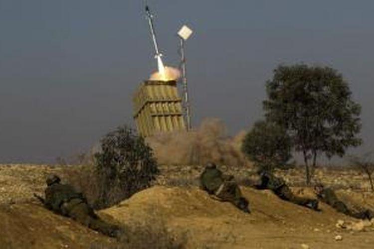 Sejumlah tentara Israel berlindung saat Iron Dome meluncurkan rudal untuk mencegat roket-roket yang ditembakan Hamas dari Gaza.