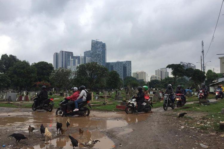 beberapa pengendara motor melewati pemakaman Menteng Pulo, Jakarta Selatan, Kamis (20/2/2020)