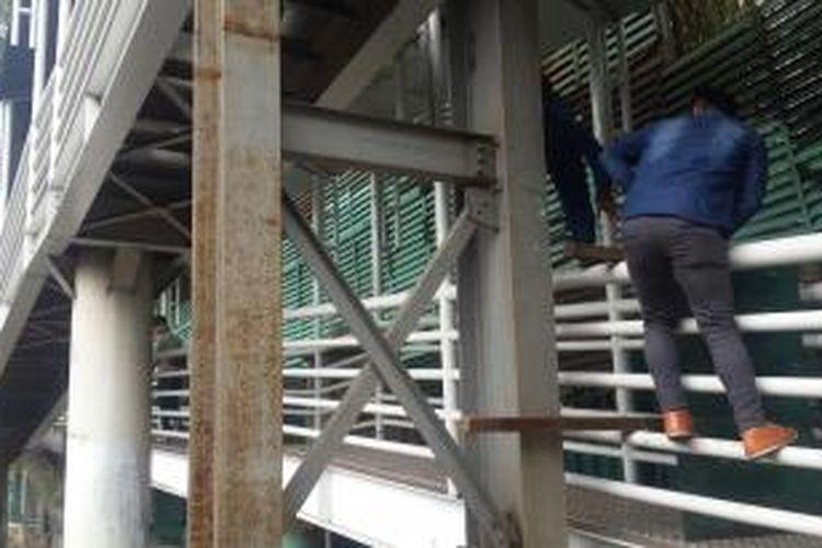 Pejalan kaki nekat panjat pagar kembatan penyebrangan orang (JPO) Halte Transjakarta Polda Metro, Jalan Jenderal Sudirman, Jakarta Pusat, Selasa (17/11/2015).