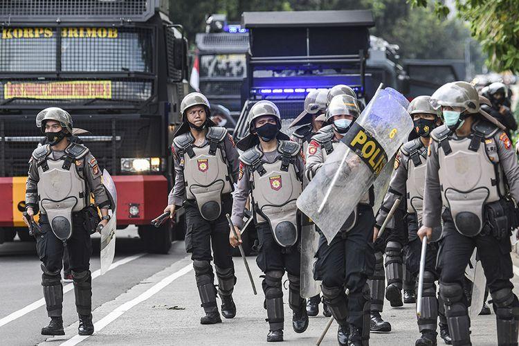 Sejumlah personel polisi bersiap untuk membubarkan massa aksi demonstrasi 1812, di kawasan Medan Merdeka Selatan, Jakarta, Jumat (18/12/2020). Kepolisian membubarkan paksa massa aksi demonstrasi dikarenakan angka penyebaran Covid-19 masih tinggi di wilayah Jakarta.