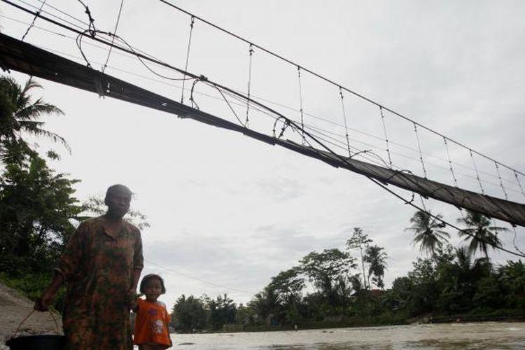 Jembatan gantung di Desa Sukajaya, Kecamatan Sajira, Kabupaten Lebak, Banten, rusak hingga tak bisa dipergunakan warga, Kamis (9/1/2014). Kawat besi jembatan yang pernah diperbaiki tahun 2011 putus dan mengakibatkan aktivitas warga terutama anak-anak sekolah dan petani terhambat. Saat air sungai Ciberang surut, warga berjalan kaki menyeberangi sungai, namun saat debit sungai meningkat mereka harus memutar jalan yang lebih jauh. KOMPAS/LUCKY PRANSISKA
