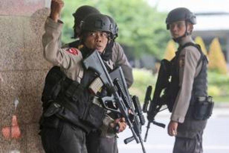 Seorang anggota polisi memberi sinyal dengan tangan kepada rekannya, saat mengejar terduga pelaku ledakan yang menghantam kawasan Jalan MH Thamrin, Jakarta Pusat, 14 Januari 2016. Serangkaian ledakan menewaskan sejumlah orang, terjadi baku tembak antara polisi dan beberapa orang yang diduga pelaku.