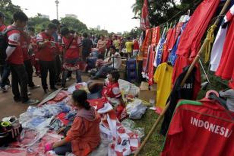 Suporter berburu atribut Arsenal yang dijual pedagang kaki lima di kawasan Stadion Gelora Bung Karno, Jakarta Selatan, Minggu (14/7/2013). Tim Indonesia akan menjalani pertandingan persahabatan dengan Arsenal.