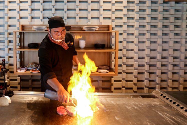 Aksi chef memasak di atas plat besi di Maison Tatsuya Teppanyaki, Kebon Sirih, Jakarta, Rabu (11/03/2020). Restoran ini menawarkan pengalaman makan dengan menyantap langsung makanan yang dimasak di depan pengunjung.