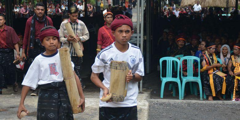 Kaum laki-laki Ngada ditugaskan untuk menyuguhkan tuak atau moke lokal untuk menggantikan minuman air setelah makan uwi (ubi) saat ritual Reba Ngada dilaksanakan di Kampung Langa, Kecamatan Bajawa, Kabupaten Ngada, Flores, NTT, Selasa (15/1/2019).