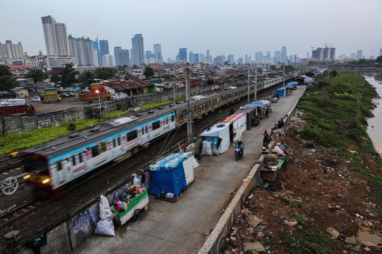 Kereta listrik (KRL) melintas di samping deretan bangunan liar di sepanjang tepi Sungai Ciliwung, Jalan Tenaga Listrik, Tanah Abang, Jakarta Pusat, Sabtu (30/9/2017). Gubuk liar kembali berdiri di sepanjang Sungai Ciliwung akibat kurangnya pengawasan dari Pemprov DKI Jakarta.