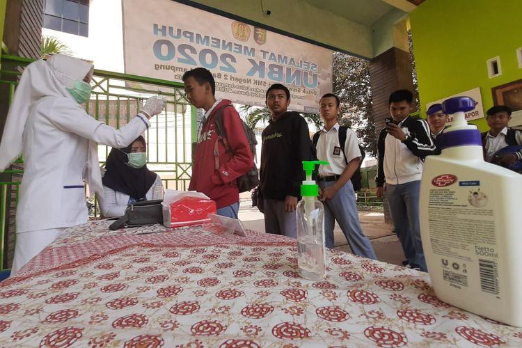 Para peserta UNBK tingkat SMK di Bandar Lampung dicek suhu tubuh sebelum masuk ruang ujian. 525 siswa mengikuti UNBK di SMKN 2 Bandar Lampung, Senin - Kamis (16-19 Maret 2020).