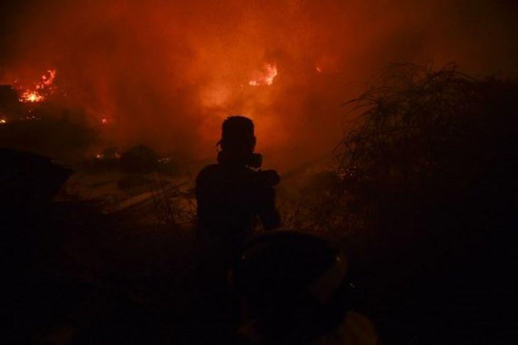 Pemadam kebakaran dan penduduk berusaha untuk mematikan api akibat kebakaran hutan di Vigo, Spanyol, pada 15 Oktober 2017.
