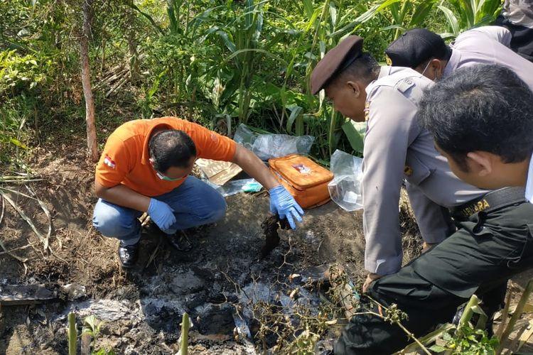 Petugas melakukan olah Tempat Kejadian Perkara (TKP), di lokasi penemuan mayat terbakar di Dusun Manyarsari Desa Gunungsari Kecamatan Dawarbladong Kabupaten Mojokerto Jawa Timur, Senin (13/5/2019).