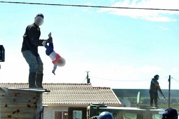 Seorang pria yang tak ingin kediamannya digusur pemerintah, naik ke atap sambil membawa anak perempuannya yang berusia satu tahun.