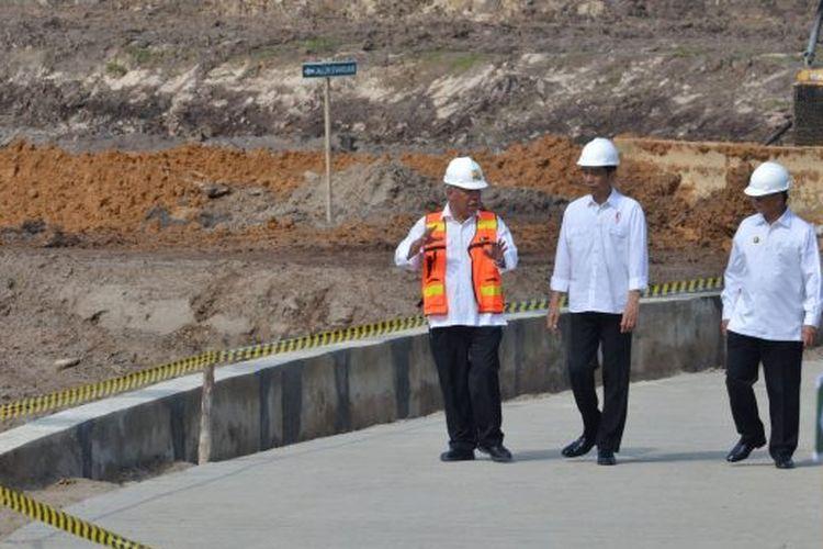 Presiden Jokowi (tengah) sedang berbincang dengan Meneri Pekerjaan Umum dan Perumahan Rakyat (PUPR) Basuki Hadimoeljono (kanan) saat mengecek salah satu proyek insfrastruktur.
