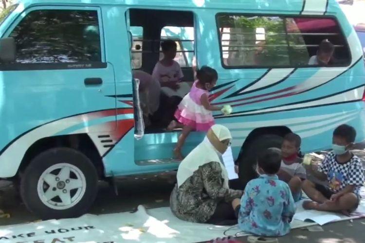 Siti Huroirohmatin (48) atau yang akrab disapa Atin, saat mengajari anak-anak di Terminal Kota Gresik.