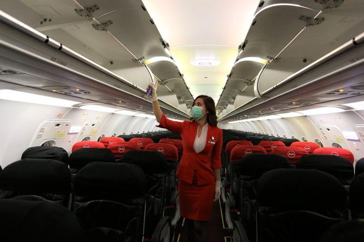 Awak kabin AirAsia terlihat membersihkan kabin dengan disinfektan