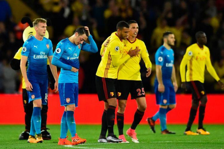Mesut Oezil tampak kecewa saat Jose Holebas dan Troy Deeney merayakan kemenangan Watford atas Arsenal di Vicarage Road, Sabtu (14/10/2017(.