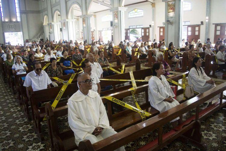 Umat Katolik duduk di kursi yang diberi pembatas garis kuning untuk memberi jarak antar umat, di Kota Borongan, Provinsi Samar, Filipina, 15 Maret 2020. Menjaga jarak aman antar warga merupakan salah satu cara yang dianjurkan untuk mencegah penyebaran virus corona.