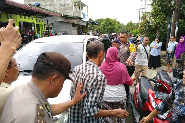 Polisi membawa tiga orang yang merupakan paman, bibi dan sepupu Rabbial M.N alias Dedek setelah menggeledah rumah di Lingkungan III, Kelurahan Sei Putih Barat, Kecamatan Medan Petisah, Rabu siang (13/11/2019).