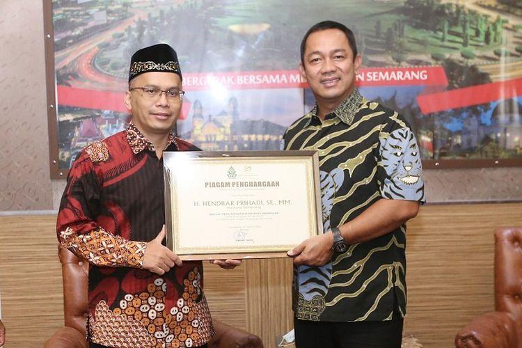 Rektor UIN Walisongo Imam Taufiq, menyerahkan piagam penghargaan kepada Wali Kota Semarang Hendrar Prihadi.